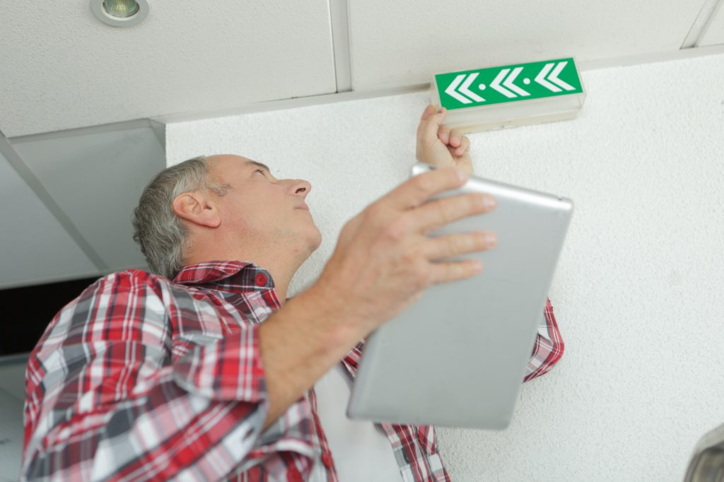 Man holding tablet, checking emergency exit sign